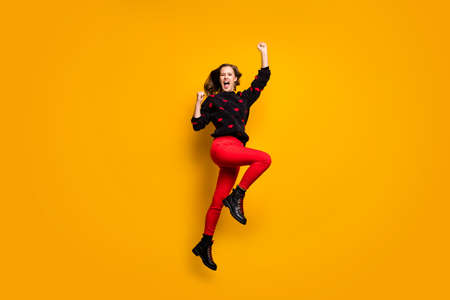 Full length profile photo of funny lady jumping up high rejoicing raising fists wild football fan wear hearts pattern sweater red trousers footwear isolated yellow color background