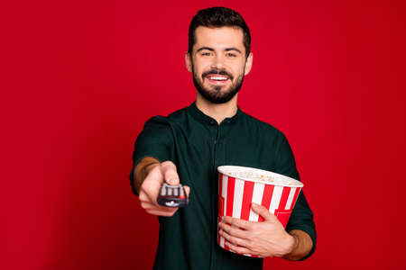 Portrait of cheerful guy have free time watch tv switch remote control hold big popcorn box enjoy emotion wear good looking outfit isolated over shine color background