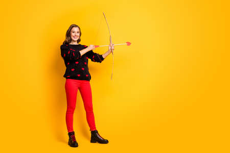 Full body profile photo of funny lady work as cupid hold bow arrow aiming feelings love couple wear hearts pattern pullover red trousers shoes isolated yellow color background Stock Photo