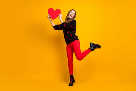 I catch you. Full length photo of pretty lady hold paper heart creative date invitation boyfriend wear hearts pattern sweater red pants shoes isolated yellow color background