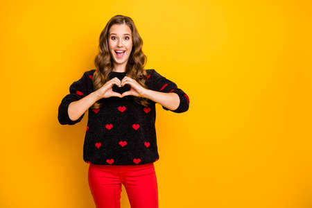 Photo of excited funny curly lady inviting boyfriend romantic date showing arms heart shape figure wear black red hearts pattern sweater trousers isolated yellow color background Banco de Imagens