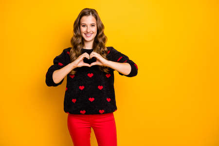 Photo of pretty curly cupid lady inviting boyfriend romantic date showing arms heart shape figure wear black red hearts pattern sweater trousers isolated yellow color background Banco de Imagens