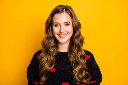Close-up portrait of her she nice attractive lovely winsome cheerful cheery wavy-haired girl wearing black pullover heart festal print isolated on bright vivid shine vibrant yellow color background