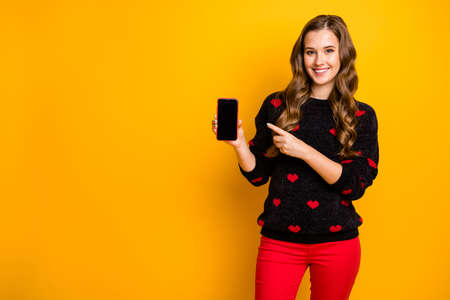 Winter season proposition. Photo of pretty lady direct finger telephone offer discount smart phone gadget price wear hearts pattern sweater red pants isolated yellow color background