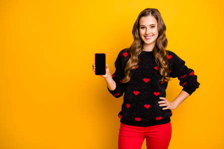Lovely holiday proposition.Photo of pretty curly lady amour holding telephone offer nice discount gadget price wear hearts pattern sweater red pants isolated yellow color background Banco de Imagens