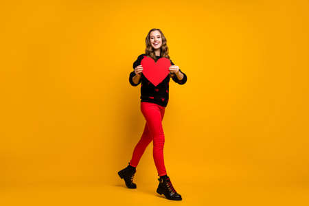Full length photo of pretty lady hold big paper heart walk street creative idea date invitation for boyfriend wear hearts pattern sweater red pants shoes isolated yellow color background