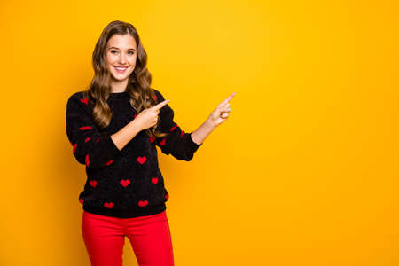 Photo of pretty lady indicating finger empty space advising low discount shopping season prices wear hearts pattern pullover red pants isolated yellow color background Banco de Imagens