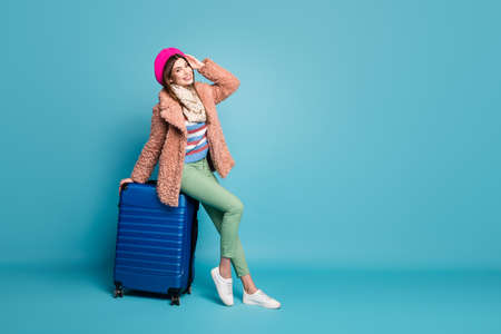 Full length body size view of nice attractive feminine cheerful cheery girl sitting on handbag cabin bag waiting departure isolated on bright vivid shine vibrant green blue turquoise color background