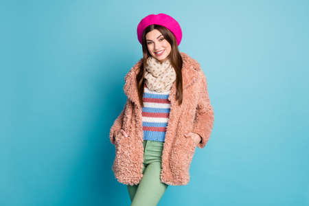 Portrait of charming lovely girl have fun fall autumn weekends put hands palm pockets wear green pants trousers jumper overcoat isolated over blue color background