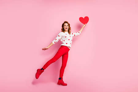 Full length body size view of her she nice attractive lovely pretty fashionable glad cheerful cheery wavy-haired girl holding in hand rising heart dream amour isolated on pink pastel color background Banco de Imagens