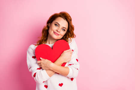 Close-up portrait of her she nice attractive lovely cheerful sweet tender gentle wavy-haired girl wearing white pullover embracing large heart isolated on pink pastel color background