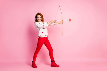 Full length body size view of her she nice attractive lovely cheerful cheery kind wavy-haired girl angel shooting arrow dream match making service isolated on pink pastel color background