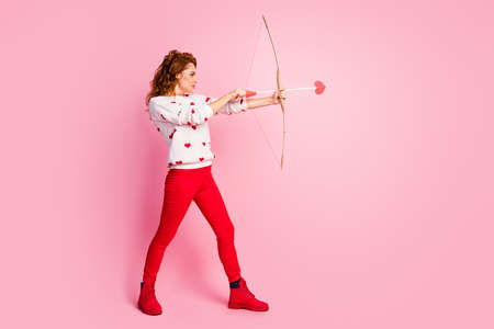 Full length body size profile side view of her she nice attractive lovely fashionable purposeful wavy-haired girl angel shooting arrow dream first date isolated on pink pastel color background Banco de Imagens