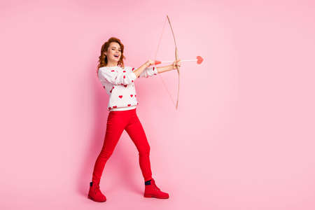 Full length body size view of her she nice attractive lovely cheerful cheery glad dreamy wavy-haired girl laughing shooting arrow gift present surprise isolated on pink pastel color background