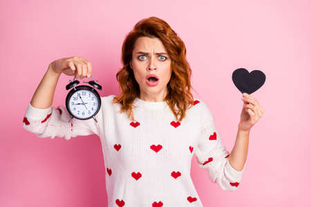 Close-up portrait of her she nice attractive pretty cute lovely worried nervous wavy-haired girl holding in hand black heart bell clock trouble stress isolated on pink pastel color background