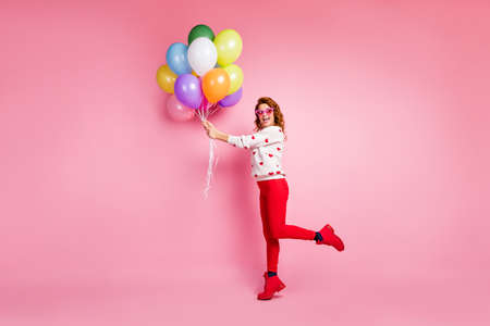 Full length body size view of her she nice attractive pretty glad cheerful cheery foxy ginger wavy-haired girl holding in hand bunch balls birthday tradition isolated on pink pastel color background