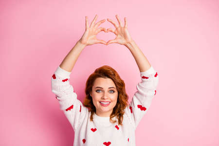 Close-up portrait of her she nice attractive lovely pretty cute cheerful cheery wavy-haired girl wearing white pullover showing heart sign over head isolated on pink pastel color background