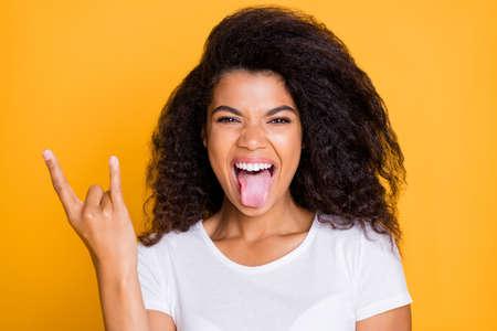Photo d'une fille folle excitée et bouclée qui crie la langue avec des doigts cornus signe de roche criant isolé en t-shirt blanc sur fond de couleur vibrante Banque d'images