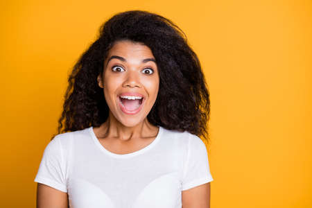 Photo of cheerful cute curly wavy nice pretty girl rejoicing about gaining victory at contests learning new information wearing white t-shirt expressing emotions on face isolated vivid color background