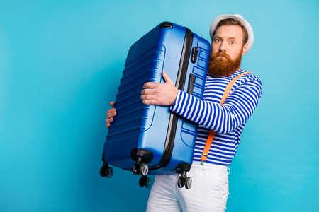 Portret van serieuze man slecht humeurig houdt zware bagage vast die hij voorbereidt op reis weekend toerisme resort luchthaven draagt goed uitziend vest geïsoleerd over blauwe kleur achtergrond Stockfoto