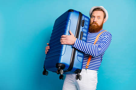 Retrato de hombre serio mal humor mantenga equipaje pesado que se prepara para el viaje de fin de semana turismo resort aeropuerto desgaste buen chaleco chaleco aislado sobre fondo de color azul Foto de archivo