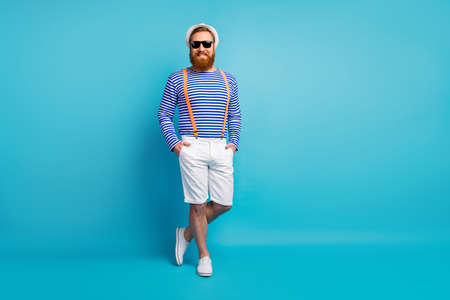 Full size photo of cheerful man enjoy free time journey put hands pocket wear look good sneakers isolated over blue color background Standard-Bild