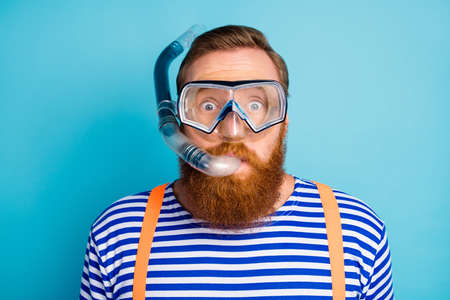 Close up photo of funky shocked red hair man watersport lover, breathe diving tube have mask wear nautical vest orange suspenders isolated over blue color background