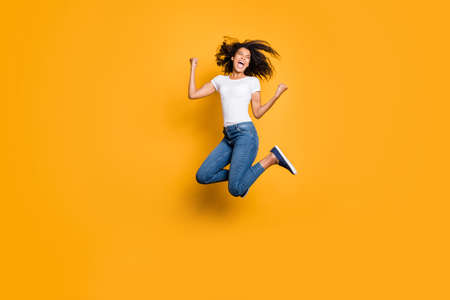 Full length body size photo of cheerful screaming shouting rejoicing overjoyed girl having won big prize wearing jeans denim white t-shirt isolated vivid color background