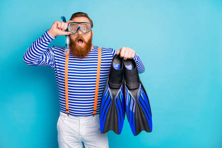 Surprised amazed redhair man impressed coral reef relax resort, sport hold flippers have breathing mask tube goggles wear white shorts orange suspenders isolated blue color background