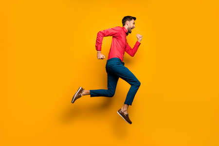 Full length profile photo of crazy funny guy jumping high up rushing black friday, shopping wear trendy red shirt bow tie pants shoes outfit isolated yellow color background