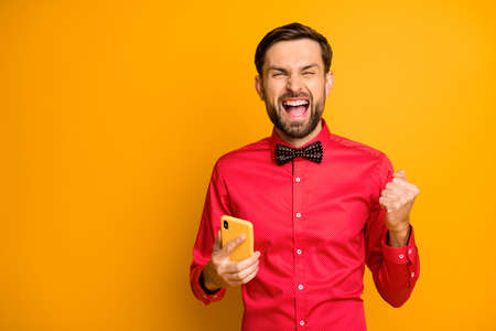 Photo of attractive guy hold telephone social network worker celebrating, growth blog popularity formalwear look trendy red shirt bow tie isolated yellow color background