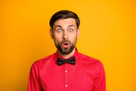 Photo of funny macho guy good mood enjoy unexpected surprise open mouth not believe eyes wear stylish red shirt with black bow tie isolated yellow color background
