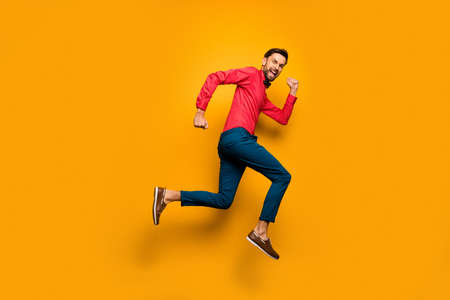Full size profile photo of funny guy jump high up rush black friday, shopping center wear trendy red shirt bow tie pants shoes outfit isolated yellow color background