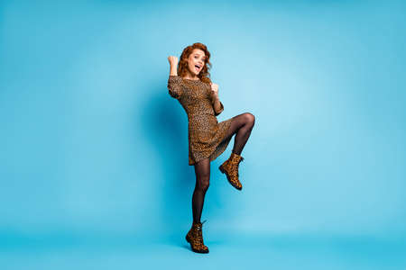 Full length photo of ecstatic cheerful woman celebrate fortune win lottery raise fists scream yeah wear season clothing boots isolated over blue color background
