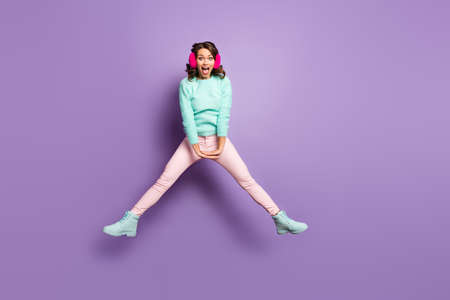 Full length photo of pretty lady jumping high up excited good mood spread legs sides having fun wear fuzzy pullover pink ear muffs pastel pants shoes isolated purple color background
