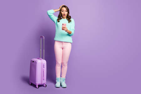 Full length photo of upset lady missed flight registration hand on head rolling suitcase watch time telephone wear fuzzy sweater pastel pink pants shoes isolated purple color background