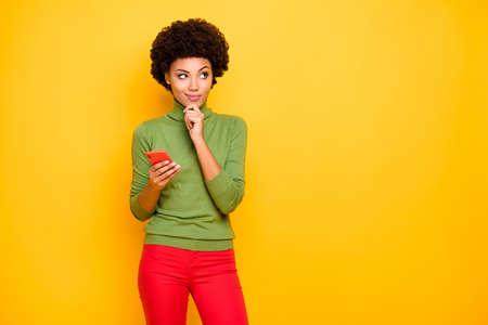 Photo d'une femme joyeuse, mignonne, mignonne et charmante, regardant dans un espace vide dans un pantalon rouge tenant un téléphone en pensant à la republiage d'un fond de couleur vibrante isolé