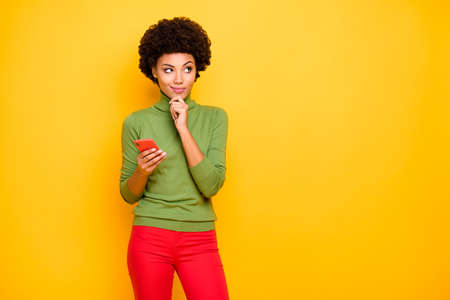 Photo of cheerful positive cute nice pretty charming woman looking up into empty space in red pants holding telephone thinking on reposting isolated vibrant color background