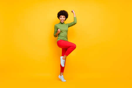 Full length body size view of her she nice attractive teenage cheerful wavy-haired girl celebrating having fun great news isolated over bright vivid shine vibrant yellow color background