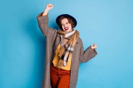Photo d'une jolie voyageuse tenant la main levée étonnée la saison des achats du vendredi noir commence à porter un élégant manteau gris long et décontracté écharpe chapeau isolé fond de couleur bleu