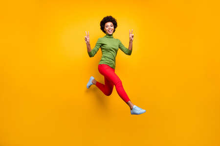 Full length body size view of her she nice attractive lovely cheerful cheery wavy-haired girl jumping showing v-sign having fun isolated over bright vivid shine vibrant yellow color background