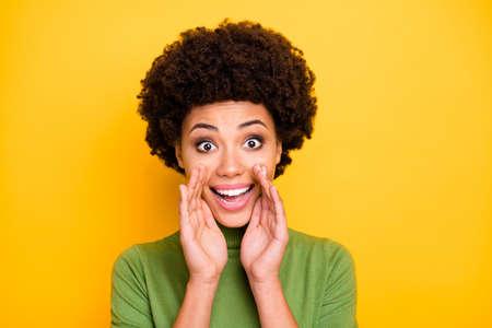Photo d'une charmante femme aux cheveux bruns bouclés ondulés positifs joyeux vous criant de bonnes nouvelles privées avec une expression de visage excitée isolée sur fond de couleur vive