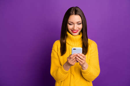 Photo of cheerful positive cute pretty nice girlfriend looking into telephone getting positive notifications long expected isolated vivid purple color background