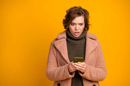 I call you later. Photo of shocked beautiful lady hold telephone read awful sms boyfriend wear casual modern style coat green knitted pullover isolated yellow color background