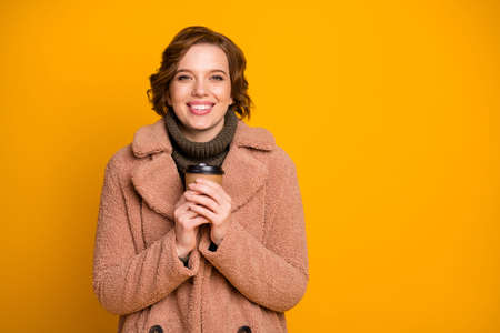 Close-up portrait of her she nice attractive lovely charming cheerful cheery girl drinking hot beverage warming up wintertime season isolated over bright vivid shine vibrant yellow color background