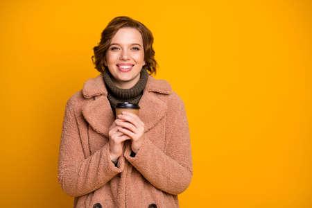 Nahaufnahmeportrait von ihr, sie schönes attraktives hübsches charmantes fröhliches fröhliches Mädchen, das heißes Getränk trinkt, das die Wintersaison aufwärmt, einzeln auf hell leuchtendem, leuchtendem, gelbem Farbhintergrund