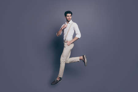 Full length profile side photo of gorgeous elegant man jump walk want, attract woman adjust button on modern shirt outfit isolated over grey color background Banque d'images