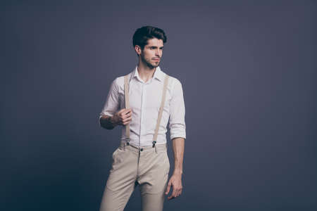Portrait of serious minded guy rich wealthy millionaire attract woman ideal man concept touch his suspenders stare copy space wear classy outfit isolated over grey color background