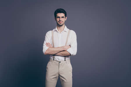 Photo of macho business man arms crossed charming smiling young reliable chief dressed formalwear white shirt beige suspenders specs pants isolated grey color background
