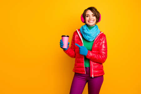Photo of pretty lady hold paper mug takeout coffee directing finger on pink cup fresh americano wear casual red coat blue scarf gloves ear covers pants isolated yellow color background